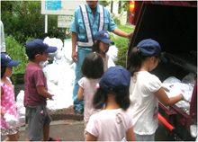 作業員監視のもと、パッカー車にゴミを投入する子どもたち
